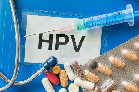 HPV virus desease concept. Many pills, syringe and stethoscope around.