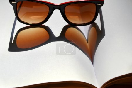 Red vintage sunglasses on a notebook giving the shadow on a heart