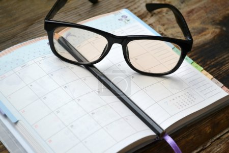 An empty retro daily planner with black pencil and reading glasses