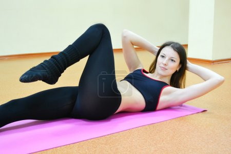 Young active woman doing Bicycle Crunch sit-up exercise in a gym