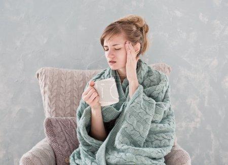 Woman with headache and tea
