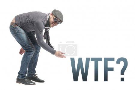 Photo for Unshaven bald man wearing a cap, jeans, sunglasses and scarf crouched and points to the inscription WTF. Isolated - Royalty Free Image