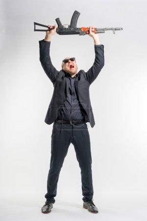 Photo pour Homme chauve en costume gris et lunettes de soleil criant avec les bras levés sur la tête. tonique - image libre de droit