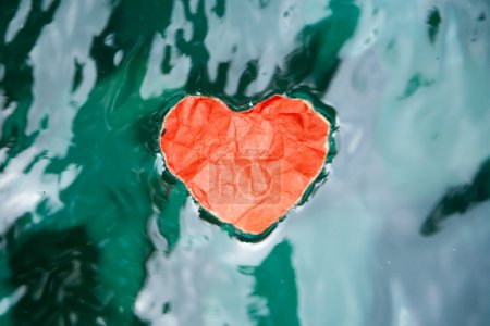 Red paper heart in the water