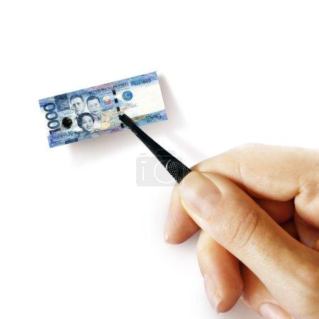 Photo pour Illustration de l'inflation - main avec un pincet tenant un petit billet de peso philippin, fond blanc - image libre de droit