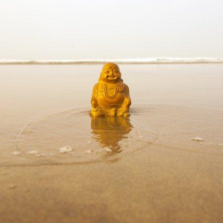 Budda statuette on the beach
