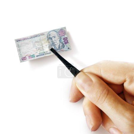 Photo pour Illustration de l'inflation - main avec un pincet tenant un petit billet de sol péruvien, fond blanc - image libre de droit