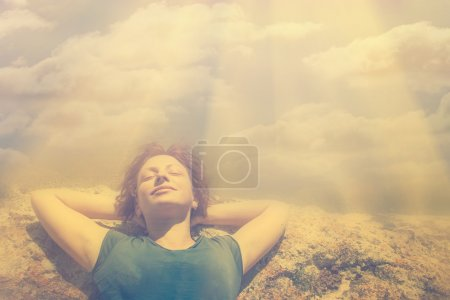 Young woman lies on top of  mountain