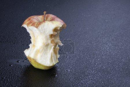 Photo pour Noyau de pomme rouge restant sur la table grise et humide, plan rapproché - image libre de droit
