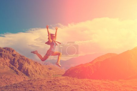 Happy girl jumping on top of rock