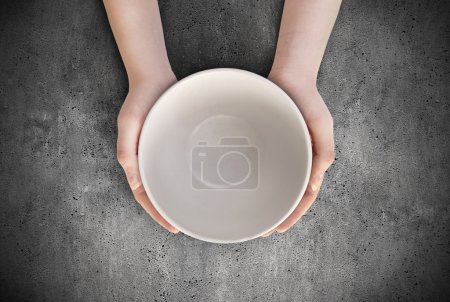 Photo for Hunger concept. Female holding empty plate waiting food. Empty plate in hand - Royalty Free Image