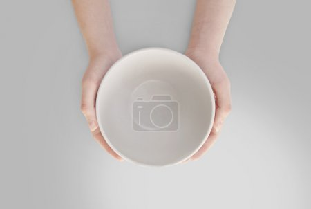 Photo for Hunger concept. Female holding empty plate waiting for food isolated. Empty plate in hand - Royalty Free Image