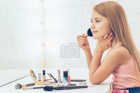 little girl applying make-up