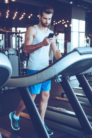 handsome man on treadmill with phone