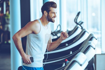 handsome man with headphones on treadmill