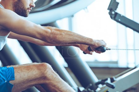 man  doing rowing at gym