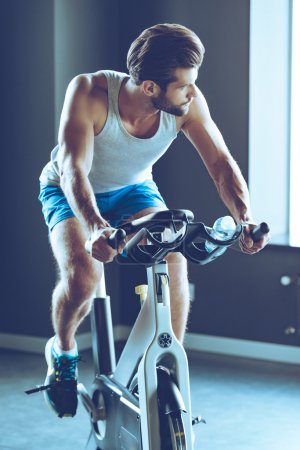 young man cycling at gym