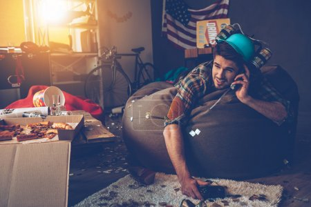 man with hangover talking on mobile phone