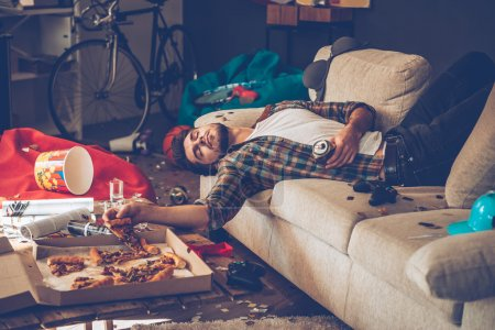 Photo for Young handsome man with hangover holding pizza slice on sofa in messy room after party - Royalty Free Image