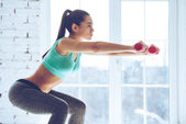 young woman doing squat with dumbbells