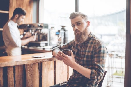 bearded man with coffee and barista