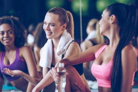 Beautiful young women sitting on exercise mat