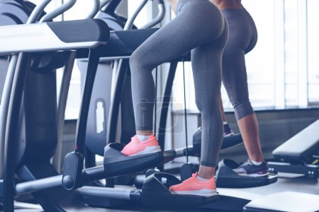 Photo for Step to beautiful body. Side view close-up part of young women working out on stepper at gym - Royalty Free Image