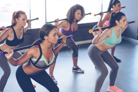 Beautiful young women exercising with barre