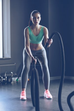 young beautiful woman working out with rope