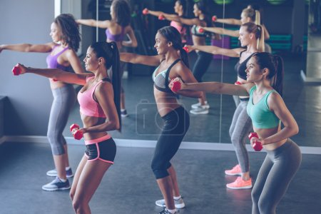 beautiful women exercising with dumbbells at gym