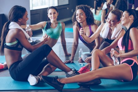 Beautiful young women sitting on exercise mat at gym