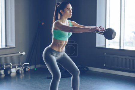 Beautiful woman working out with kettle bell at gym