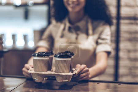 Photo pour Partie de la jeune femme africaine joyeuse en tablier tenant des tasses à café en se tenant debout au café - image libre de droit