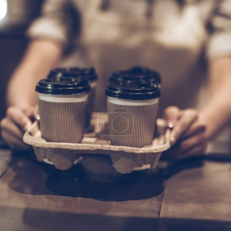 Photo for Close-up of woman serving coffee to go while standing at the wooden bar counter - Royalty Free Image
