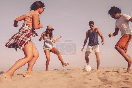 best friends playing beach football