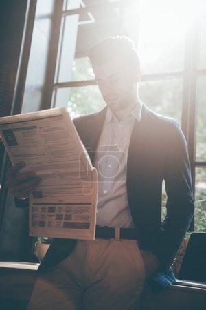 Photo pour Homme d'affaires, lisant le journal dans son bureau à domicile - image libre de droit
