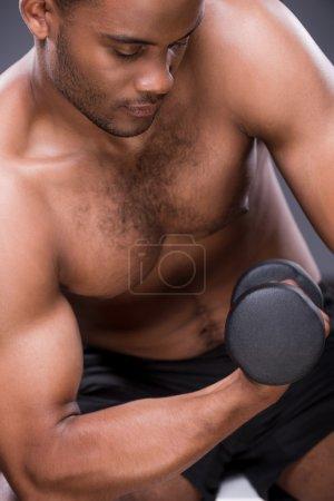 Weight exercises. Young shirtless African man exer...