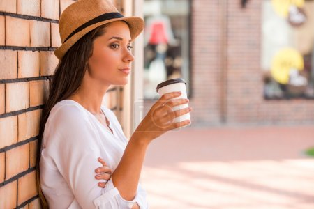 Woman in funky hat holding cup with hot drink