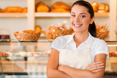 Photo for I love my job! Beautiful young woman in apron keeping arms crossed while standing in bakery shop - Royalty Free Image