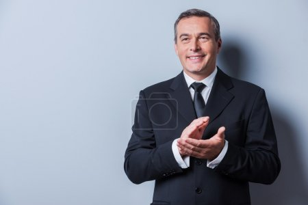 Mature man in formalwear clapping hands