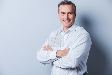 Photo for Confident mature man. Portrait of confident mature man in shirt looking at camera and smiling while keeping arms crossed and standing against grey background - Royalty Free Image