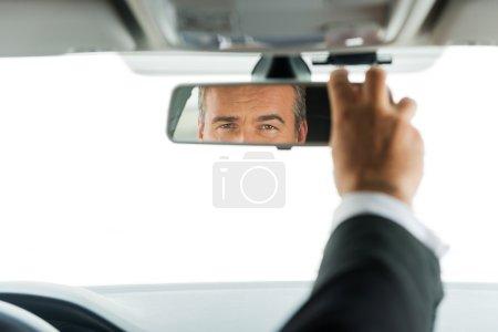 Mature man in formalwear adjusting mirror in car