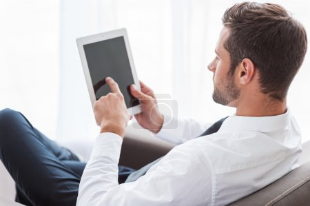 Businessman in shirt and tie working on digital tablet