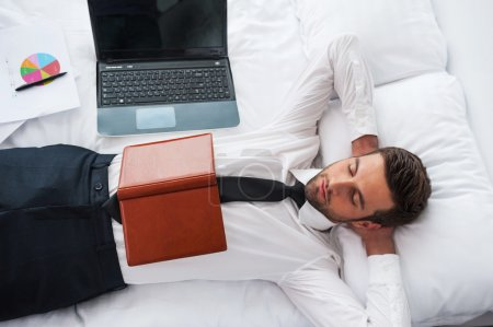 Man in shirt and tie lying in bed at hotel room