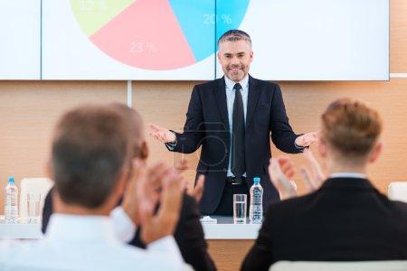 Photo pour . Homme mûr confiant dans les gestes et le sourire de formalwear tout en faisant une présentation dans la salle de conférence avec des gens applaudissant au premier plan - image libre de droit