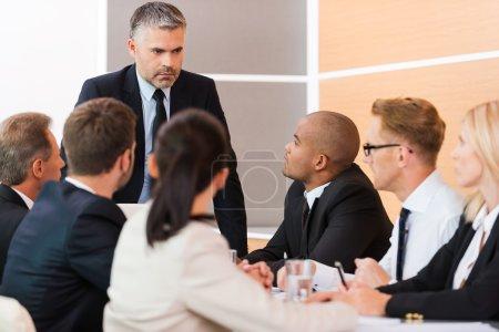 Photo pour Réunion urgente. gens d'affaires vetu assis à la table tandis que leur patron permanent et à les regarder - image libre de droit