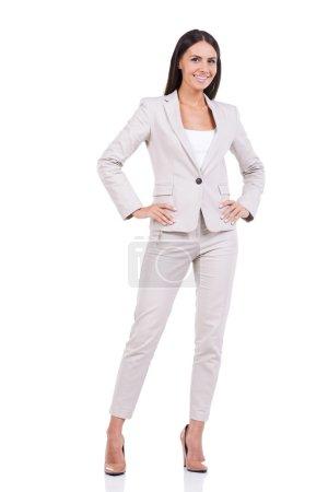 Photo pour Femme d'affaires confiant. toute la longueur du confiant jeune femme d'affaires en costume tenue les mains sur les hanche et souriant tout en se tenant sur fond blanc - image libre de droit