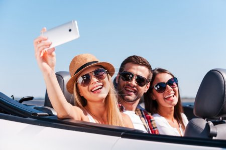 Photo for Catching a happy moment. Three young happy people enjoying road trip in their white convertible and making selfie - Royalty Free Image