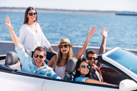 Photo for Great day for a ride. Group of young happy people enjoying road trip in their white convertible and raising their arms - Royalty Free Image