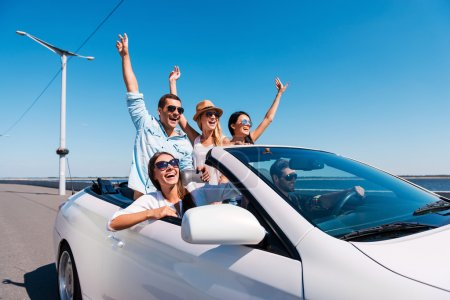 Photo for Nothing but friends and road ahead. Group of young happy people enjoying road trip in their white convertible and raising their arms up - Royalty Free Image